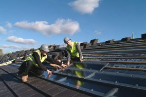 povey communications - men installing solar roof tiles